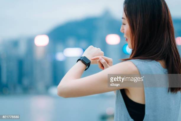 Young woman checking health status with smart watch in city