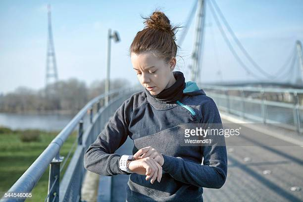 Young woman checking heart rate monitor after jogging