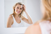 Young woman checking her hair in bathroom mirror at home