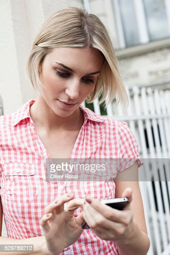 Young woman checking her smartphone : ストックフォト