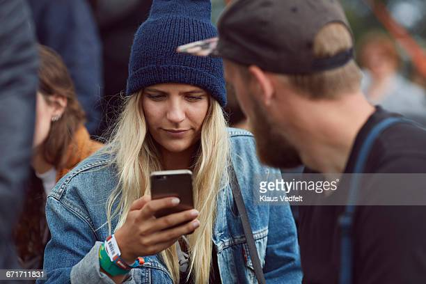 Young woman checking phone at festival