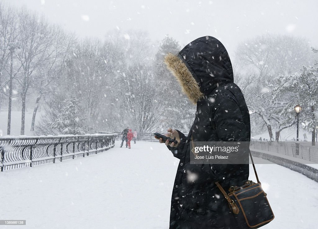 Young woman checking phone in snow : Stock Photo