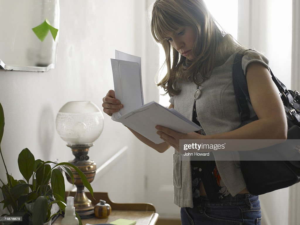 Young woman checking post in hallway : Stock Photo