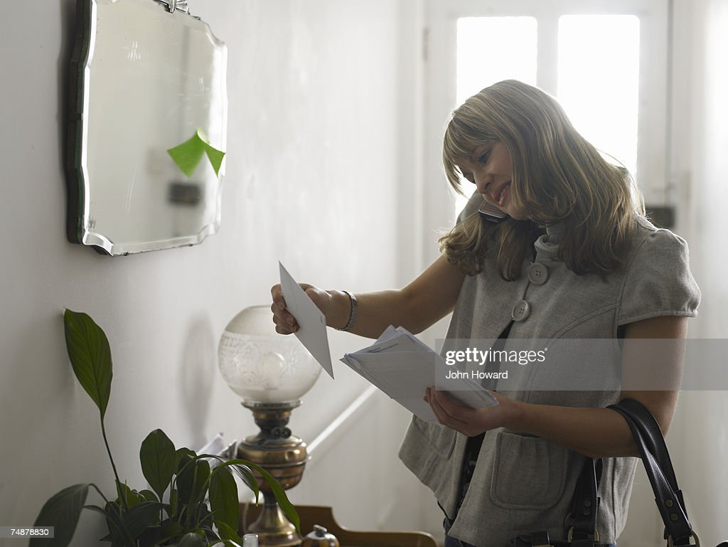 Young woman checking post in hallway, using cell phone, smiling : Stock Photo
