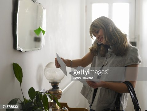 Young woman checking post in hallway, using cell phone, smiling : Bildbanksbilder