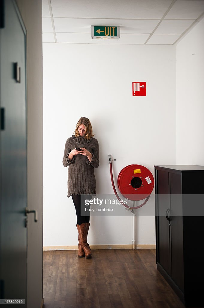 Young woman checking social media on her phone in the hallway.