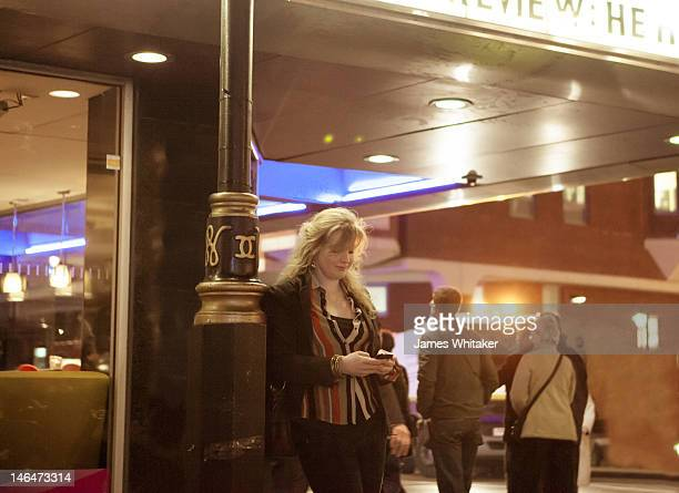 Young woman checks phone outside cinema
