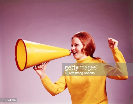 Young woman cheerleader in yellow turtleneck sweater, yelling into yellow megaphone. (Photo by H. Armstrong Roberts/Retrofile/Getty Images) : Stock Photo
