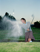 Young woman chipping ball out of bunker, sand flying