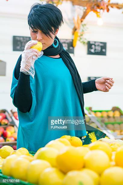 Young woman choosing and sniffing lemons