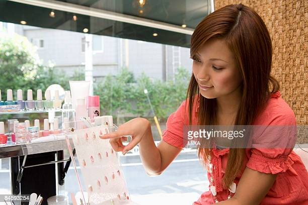 Young woman choosing artificial nails