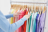 Young woman choosing clothes from colorful rack