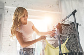 Attractive young woman is choosing clothes in light room. Girl in wardrobe.