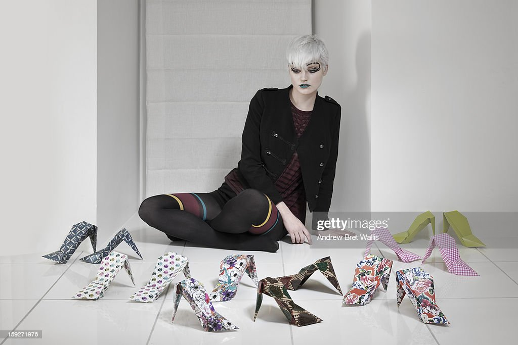 young woman choosing from a range of origami shoes : Stock Photo