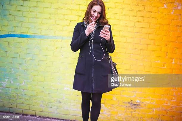 Young woman choosing music on city street