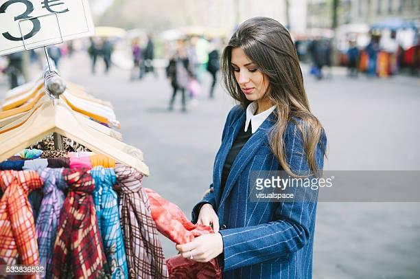 Jeune femme choisissant écharpes dans une rue boutique