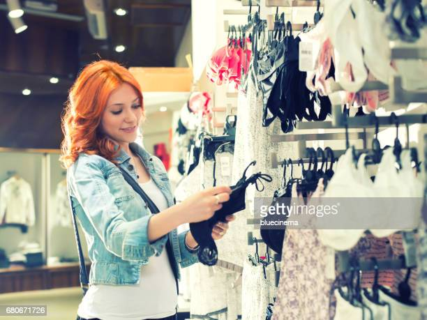 Young woman choosing underwear at clothing store
