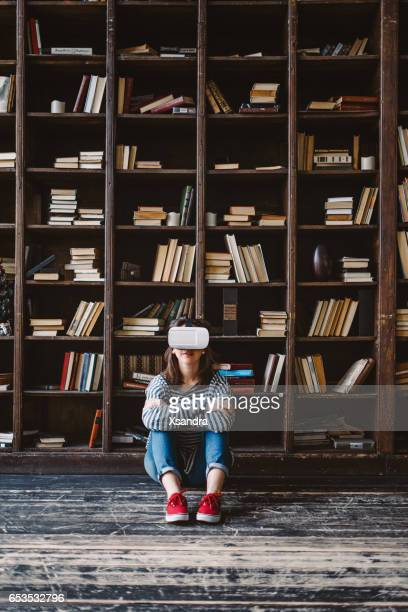 Young woman choosing VR Glasses over books