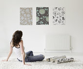 Young woman choosing wall paper for home