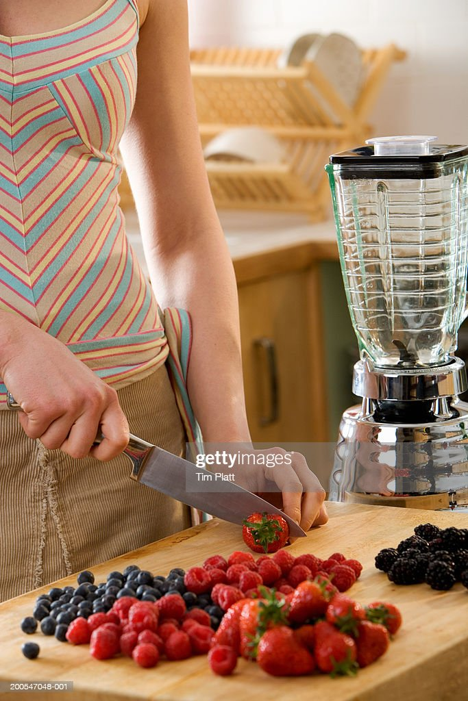 Young Woman chopping berries in kitchen, close-up, mid section : Stock Photo