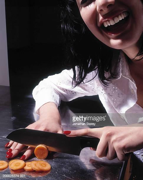 Young woman chopping carrot, laughing