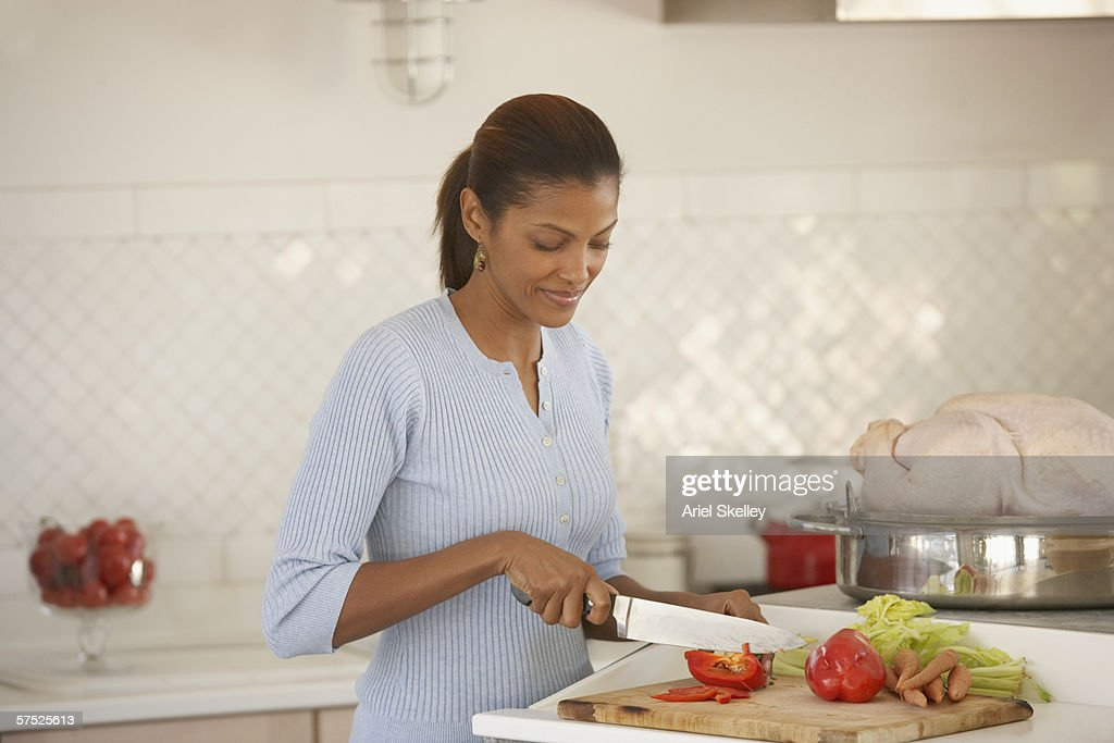 Young woman chopping vegetables : Stock Photo