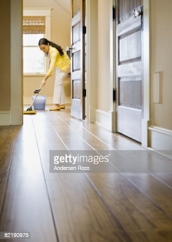 Young Woman cleaning a Floor with a Mop : Stock Photo
