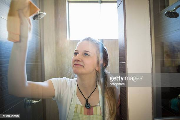 Young woman cleaning bathroom with green cleaning products