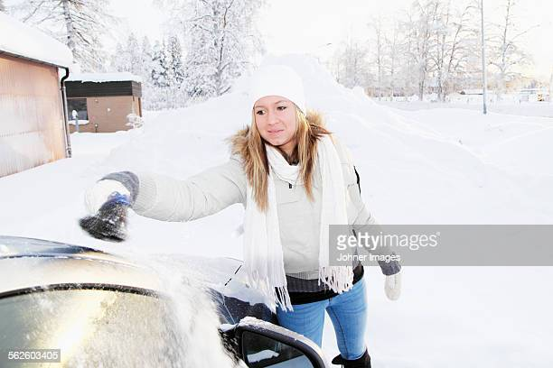 Young woman cleaning car at winter