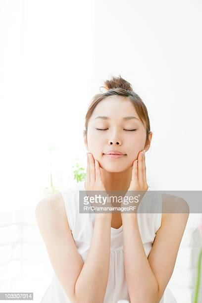 Young woman cleaning her face