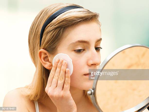 Young woman cleaning her face with a cotton pad