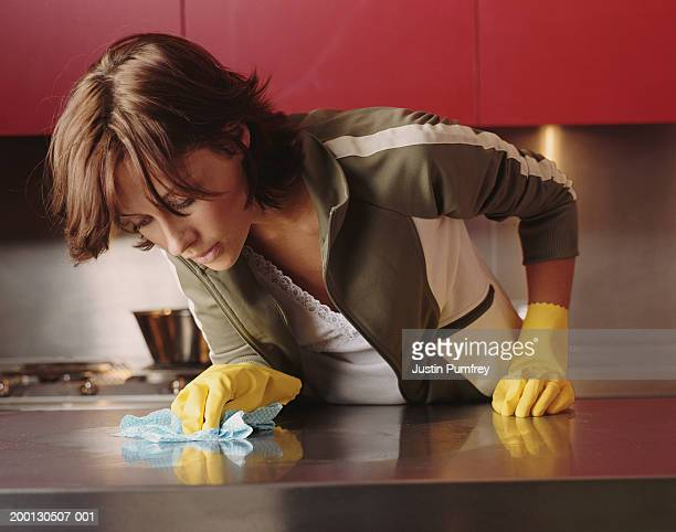 Young woman cleaning kitchen counter