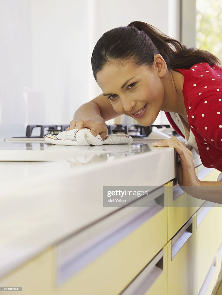 Young woman cleaning kitchen surface : Stock Photo