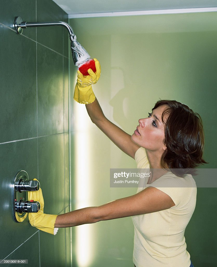 Young woman cleaning shower head : Stock Photo