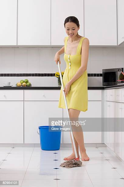 Young woman cleaning the floor with a mop