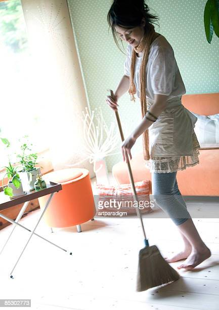 Young woman cleaning up the room