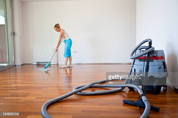 Young woman cleaning wooden floor