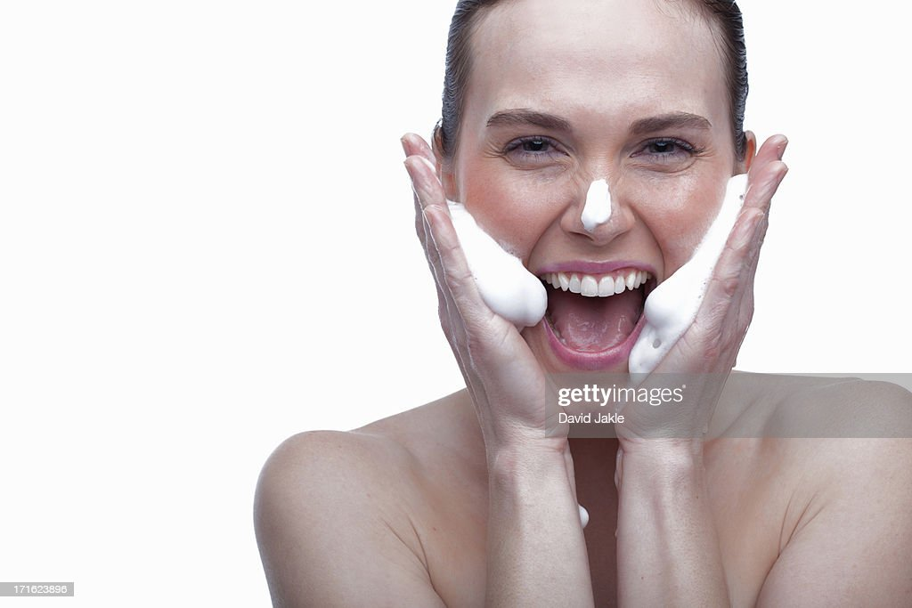 Young woman cleansing face : Stock Photo