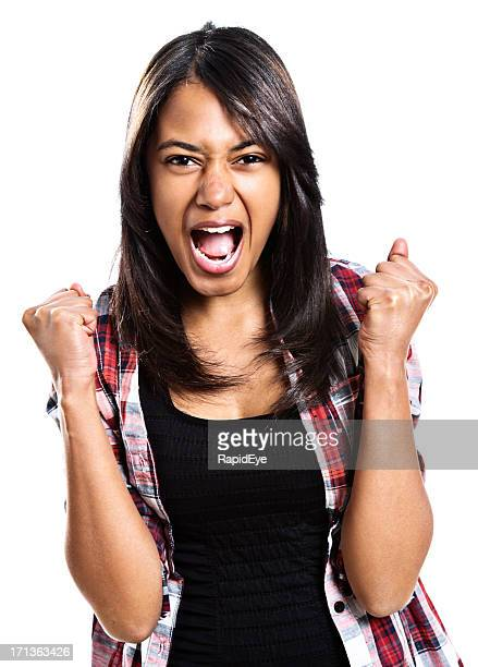 Young woman clenches fists and yells, either encouraging or furious