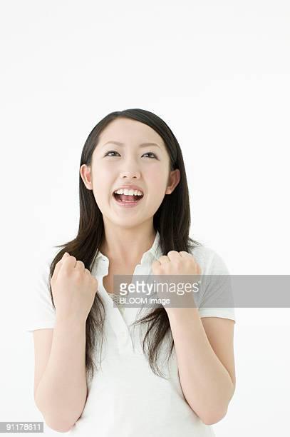 Young woman clenching fists, portrait, studio shot