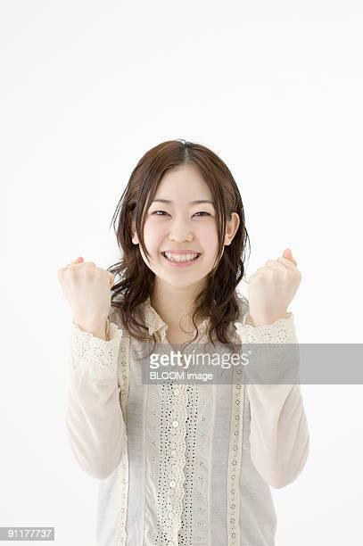 Young woman clenching fists, studio shot