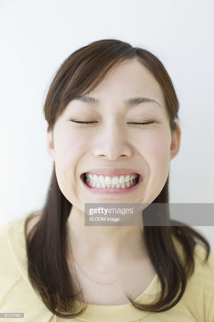 Young Woman Clenching Teeth With Eyes Closed Portrait