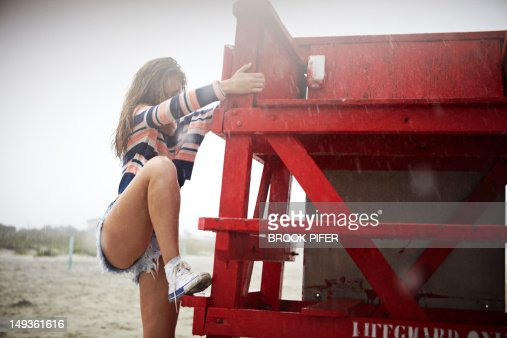 Young woman climbing chair on beach in rain : Stock Photo