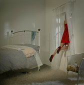 Young woman climbing out of bedroom window.
