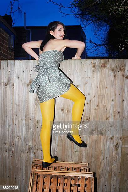 Young woman climbing over garden fence, laughing