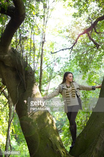 Young woman climbing tree : Stock Photo