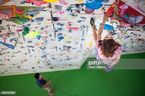 A young woman climbs a rock climbing wall