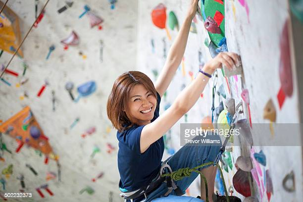 A young woman climbs at a rock climbing gym
