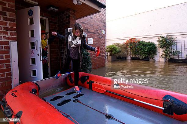 A young woman climbs onto a lifeboat in Skeldergate on December 29 2015 in York England Heavy rain over the Christmas period has caused severe...