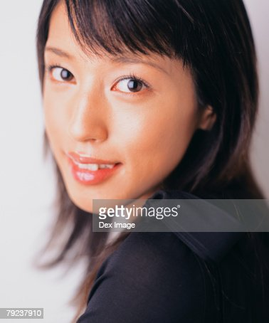 Young woman, close-up, looking over shoulder, portrait : Stock Photo